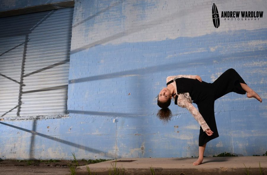 Dancer does a pose against blue wall during a Panama City dance photographer session.