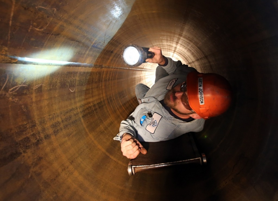 ustin Johnson visually inspects the inside of a pipe at Berg Steel Pipe Corp. in Panama City. (Panama City Photographer | Andrew Wardlow)