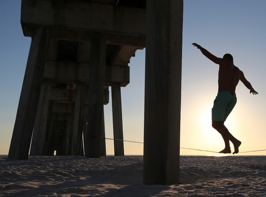 Andrew Heymann walks a slackline beneath the M.B. Miller County Pier in Panama City Beach. Slacklining differs from tight wires and tightropes in that they are tensioned to create a line with bounce and stretch like a long and thin trampoline. (Panama City Photographer | Andrew Wardlow)