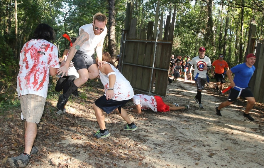A runner narrowly escapes a group of zombies during third annual Running Scared Zombie 5k Run at Harder