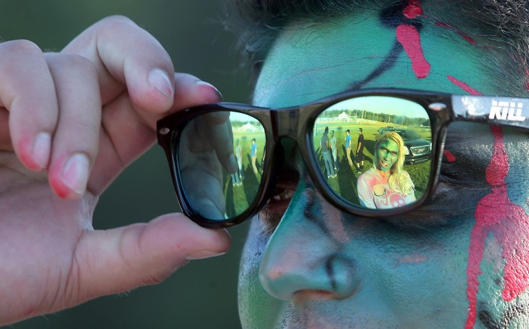 Misty Gutshall is reflected in Christopher Gil's sunglasses at the third annual Running Scared Zombie 5k Run at Harder's Park in Panama City. (Panama City Photographer/Andrew Wardlow)