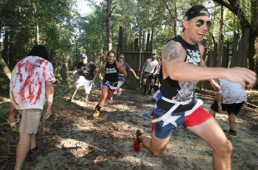 Runners attempt to avoid the zombies during the third annual Running Scared Zombie 5k Run at Harder