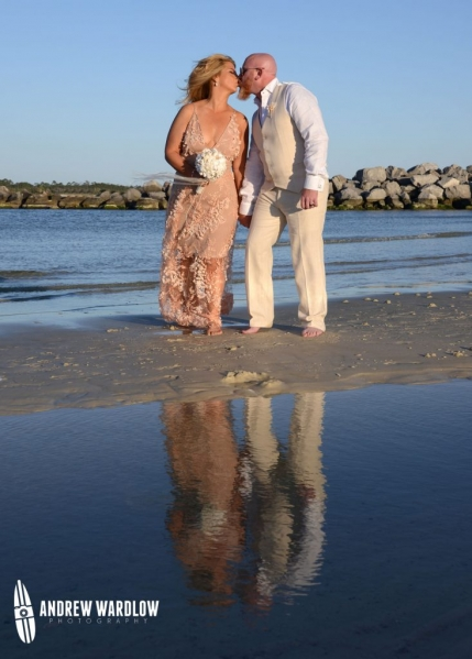 Man and woman kissing with their reflection in the water at St. Andrews State Park in Panama City Beach, Florida taken by Panama City Beach photographer Andrew Wardlow.